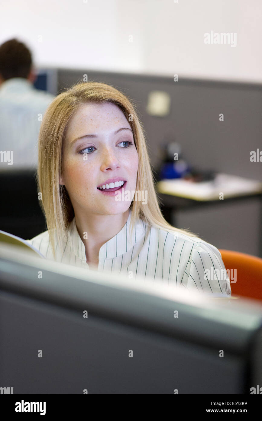 Intern cheerfully working in office cubicle - Stock Image