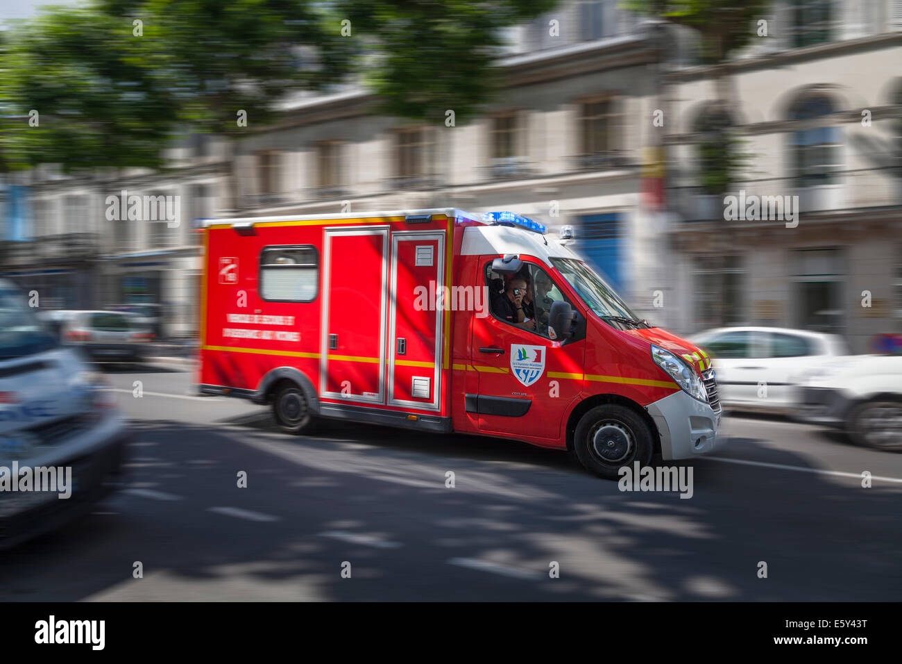 Blurred French emergency vehicle rushing through city street with blue lights flashing. - Stock Image
