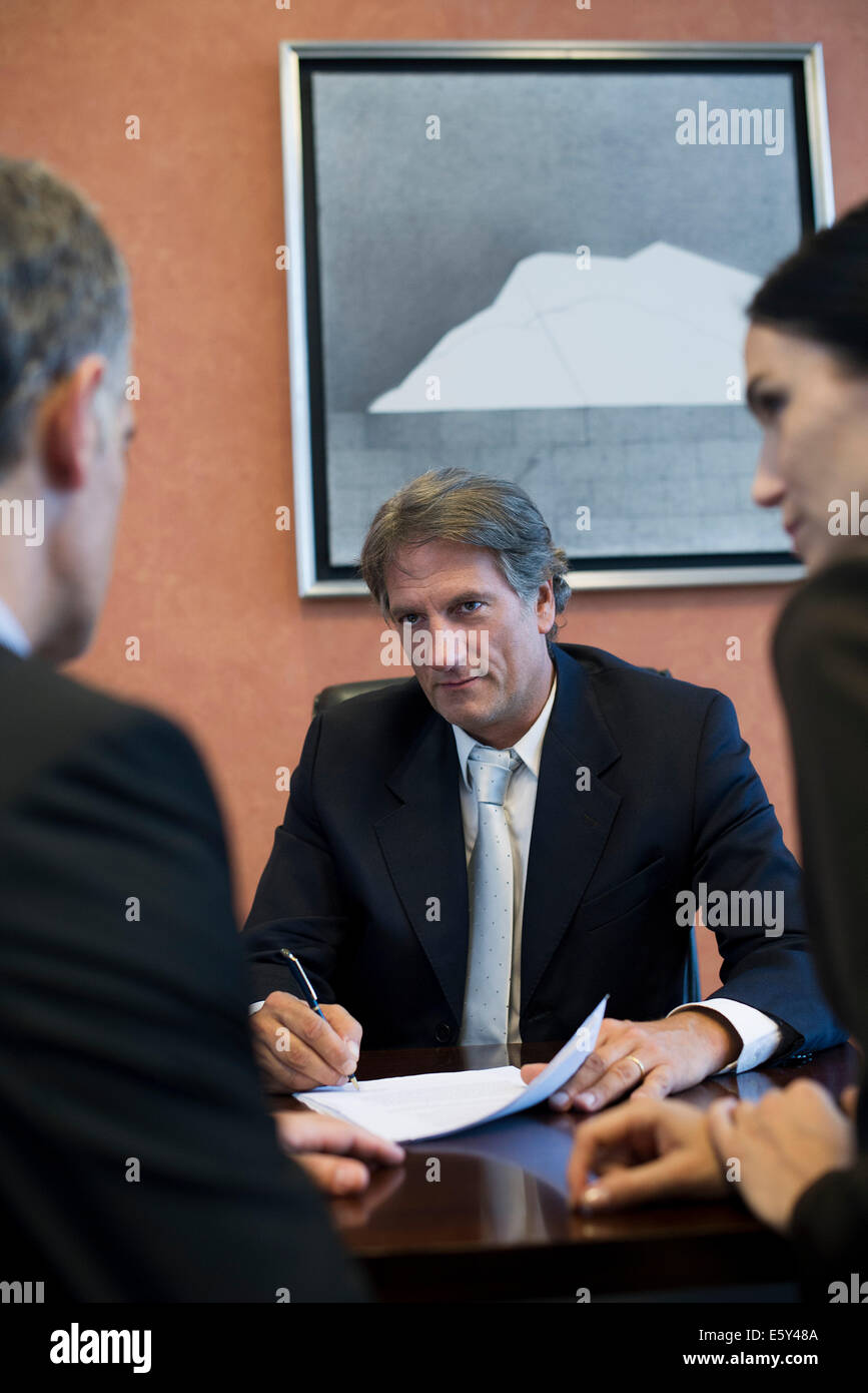 Business meeting, associates watch as businessman signs document - Stock Image