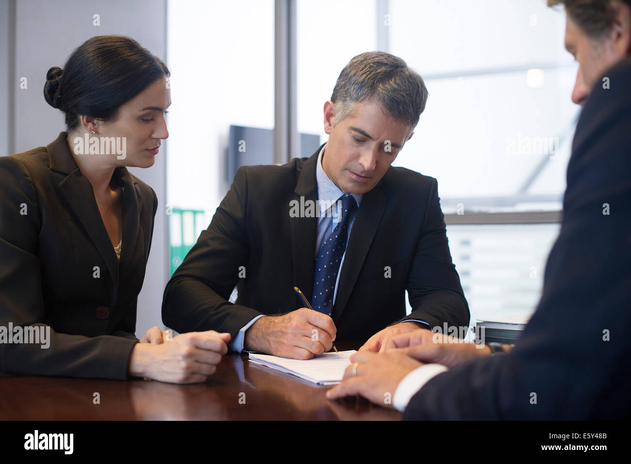 Business meeting, businessman signing document while associates observe - Stock Image