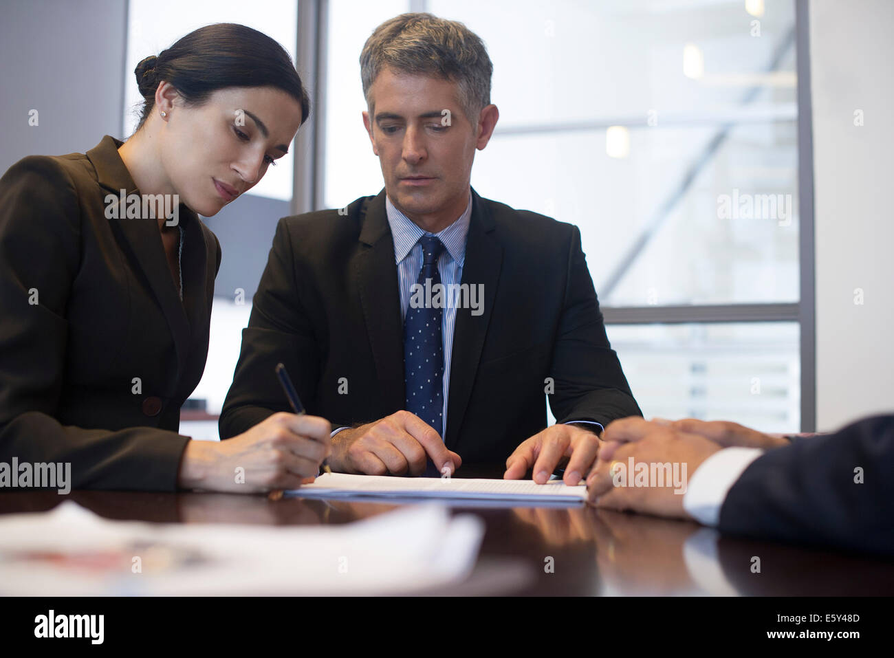 Business meeting, businesswoman signing document while associates observe - Stock Image