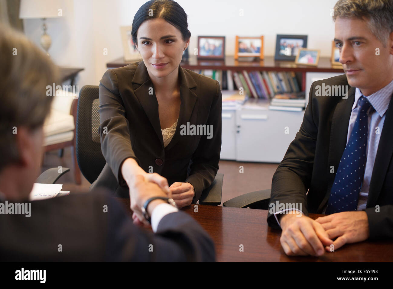 Business meeting, businesswoman shaking hands with associate - Stock Image