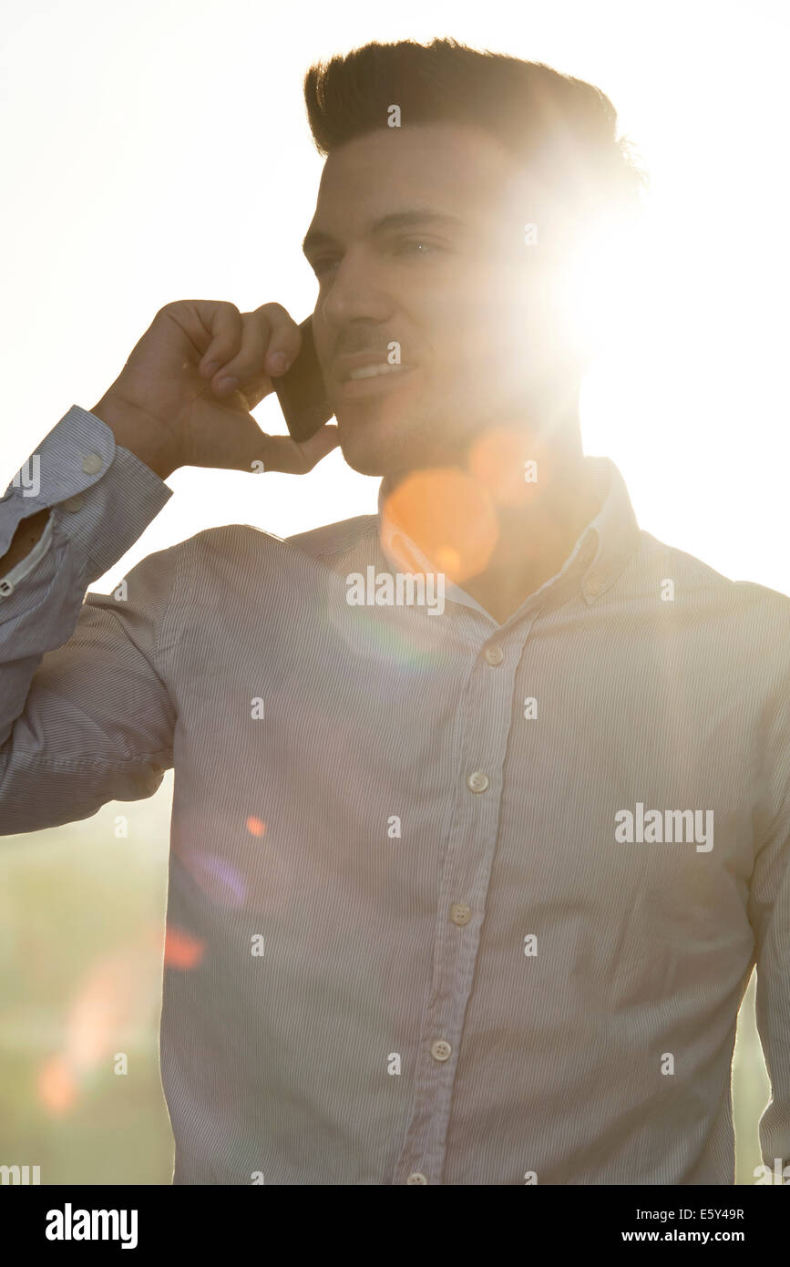 Young man talking on cell phone, silhouette - Stock Image