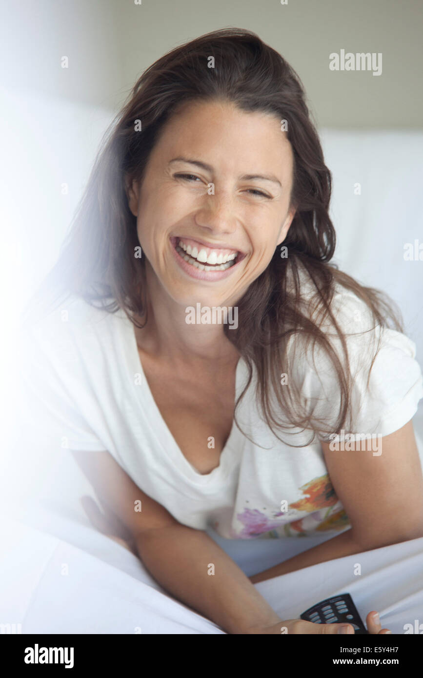 Woman laughing while watching TV in bed - Stock Image