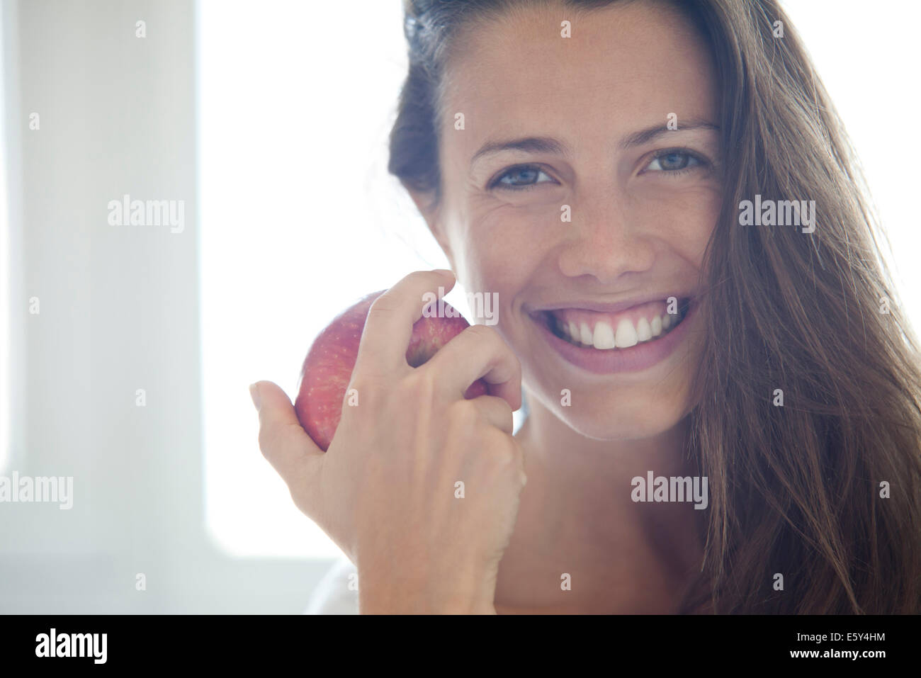 Woman holding apple, portrait - Stock Image