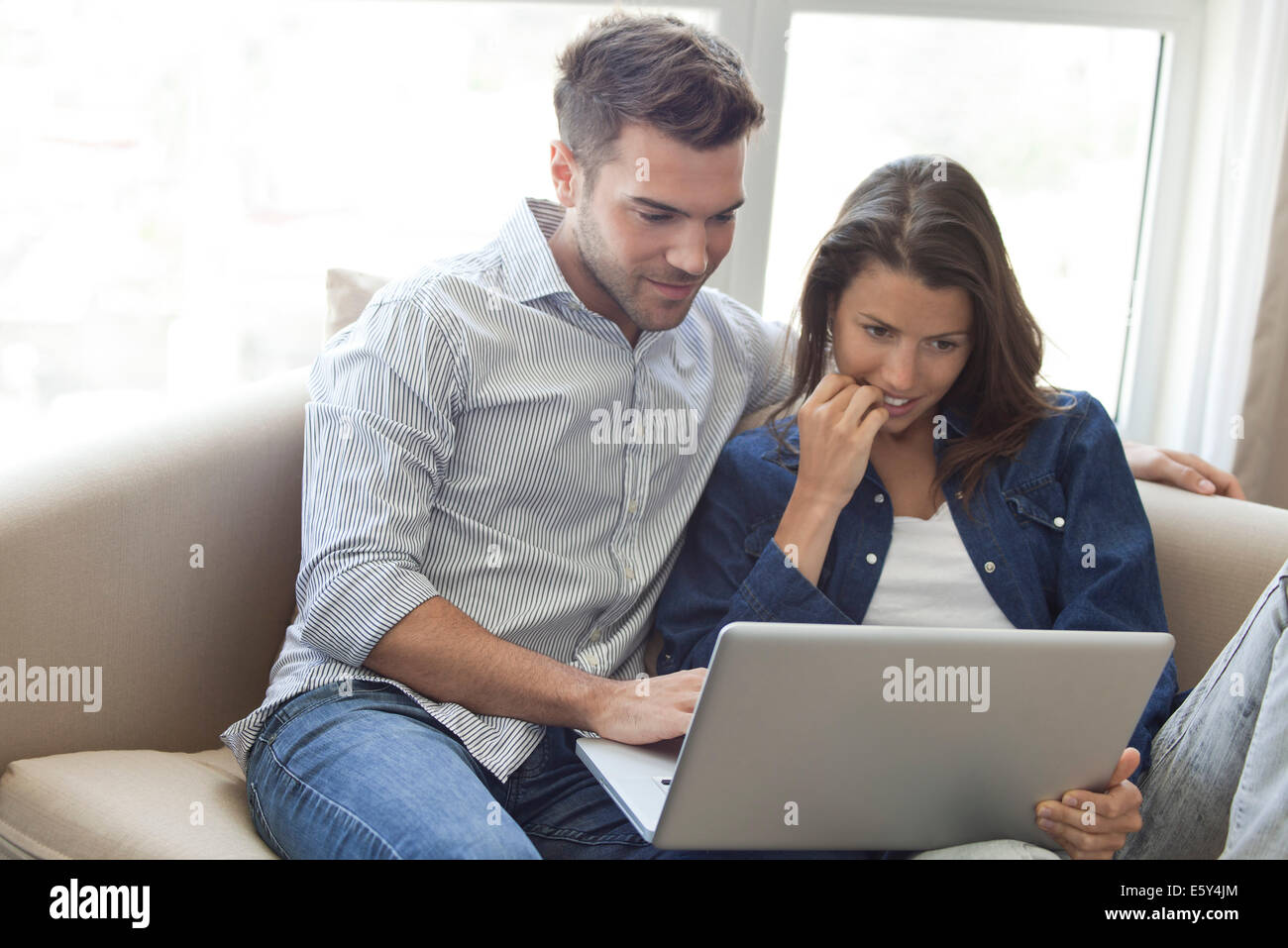 Couple using laptop computer together at home - Stock Image