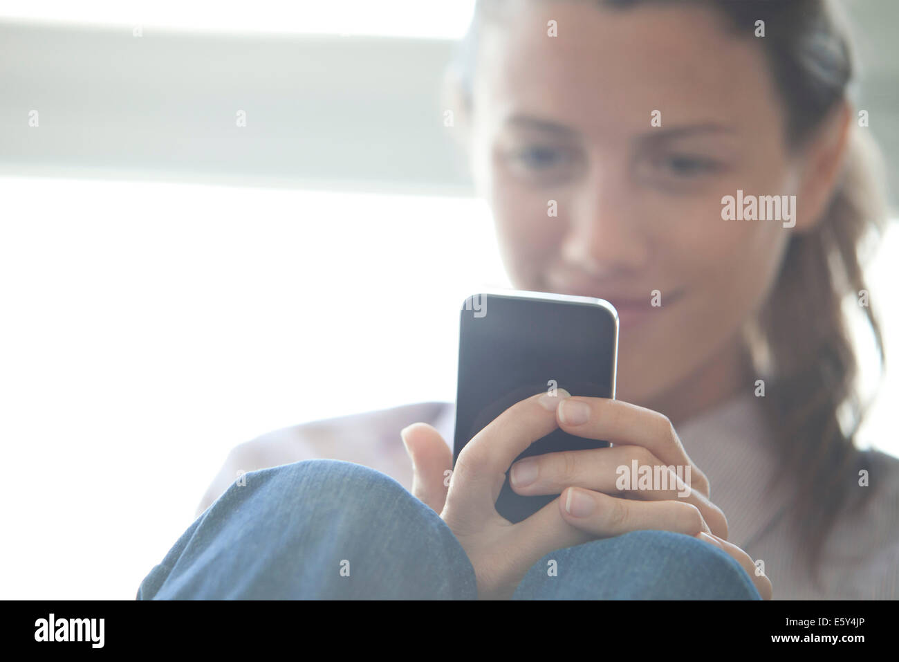 Woman browsing web with smatrphone - Stock Image