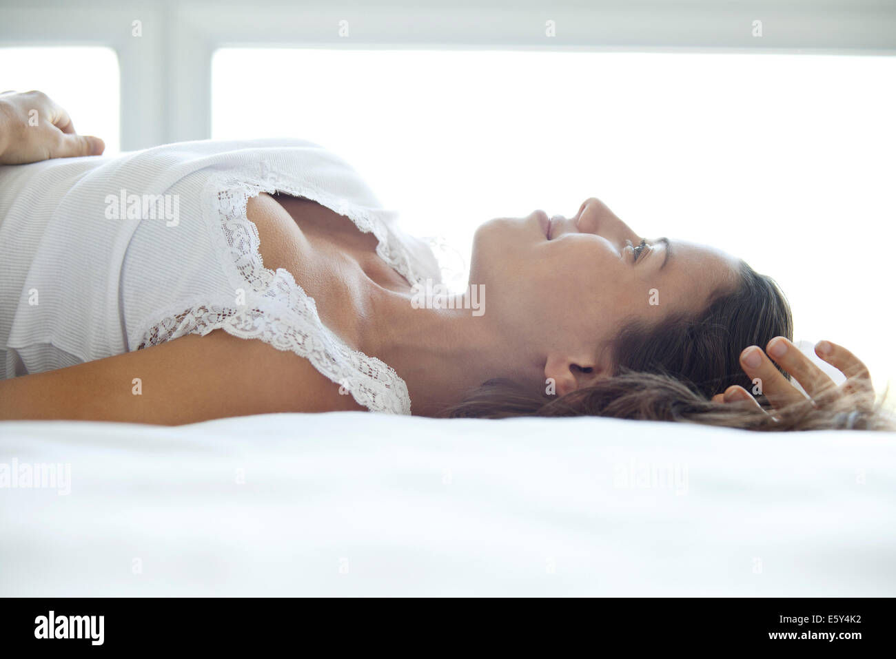 Woman lying on bed, looking up and smiling dreamily - Stock Image