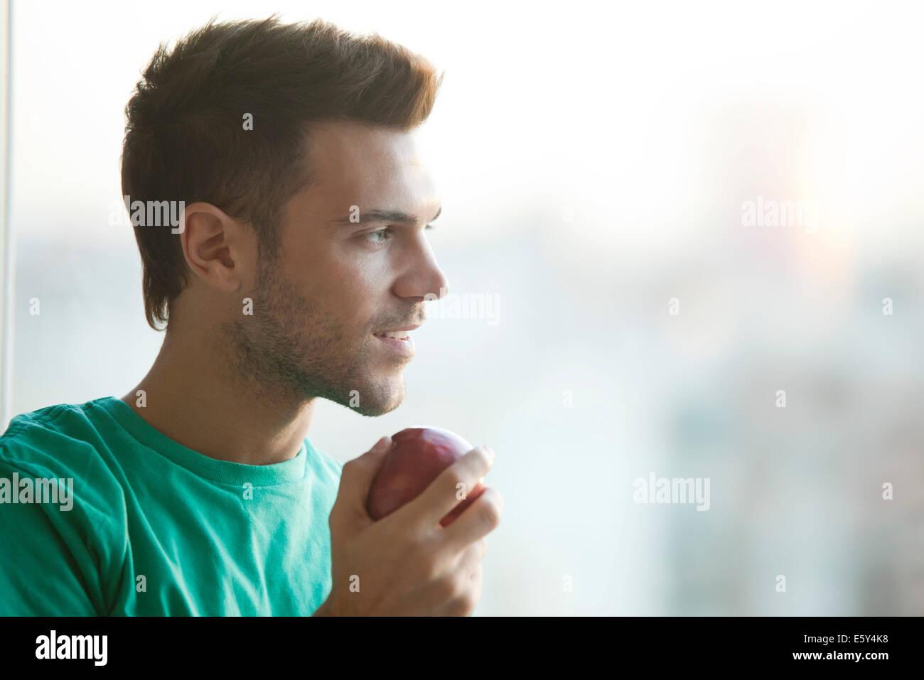 Man holding apple, gazing out window - Stock Image