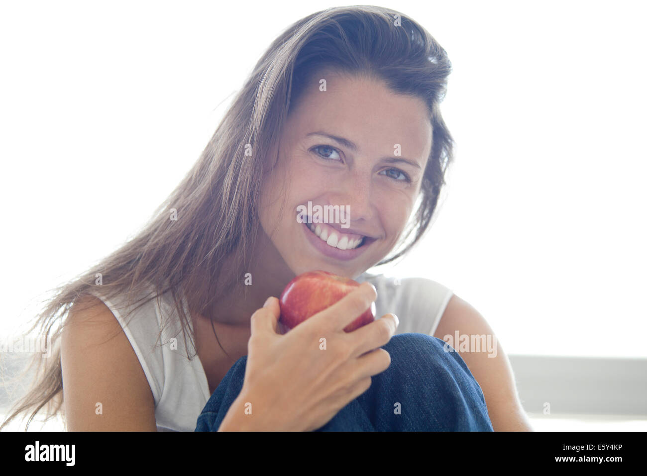 Woman holding apple, smiling, portrait - Stock Image