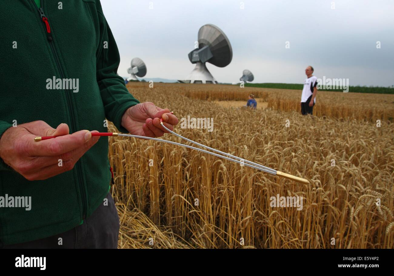 Raisting, Germany. 26th July, 2014. A man walks with a wiggle stick across a cornfield passing nearby radio antennas - Stock Image