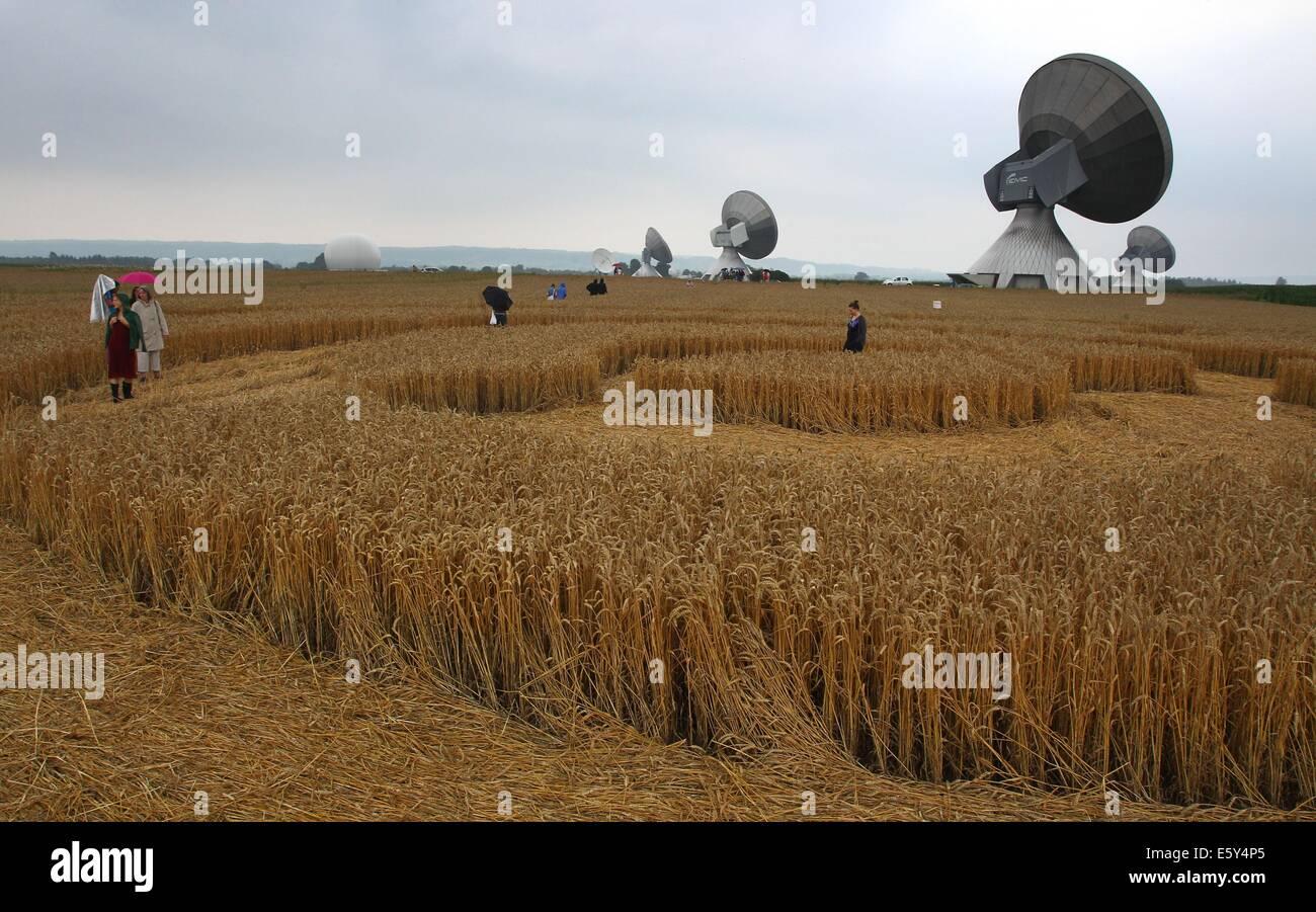 Raisting, Germany. 26th July, 2014. Excursionists walk across a cornfield passing nearby radio antennas near Raisting, - Stock Image