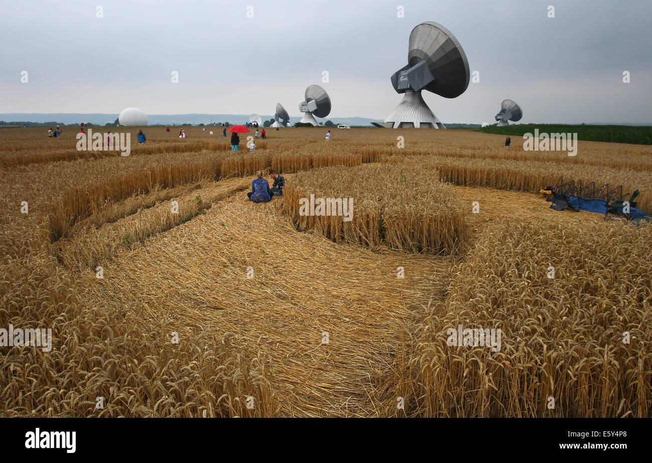 Raisting, Germany. 26th July, 2014. Excursionists sit in a cornfield passing near a set of radio antennas near Raisting, - Stock Image