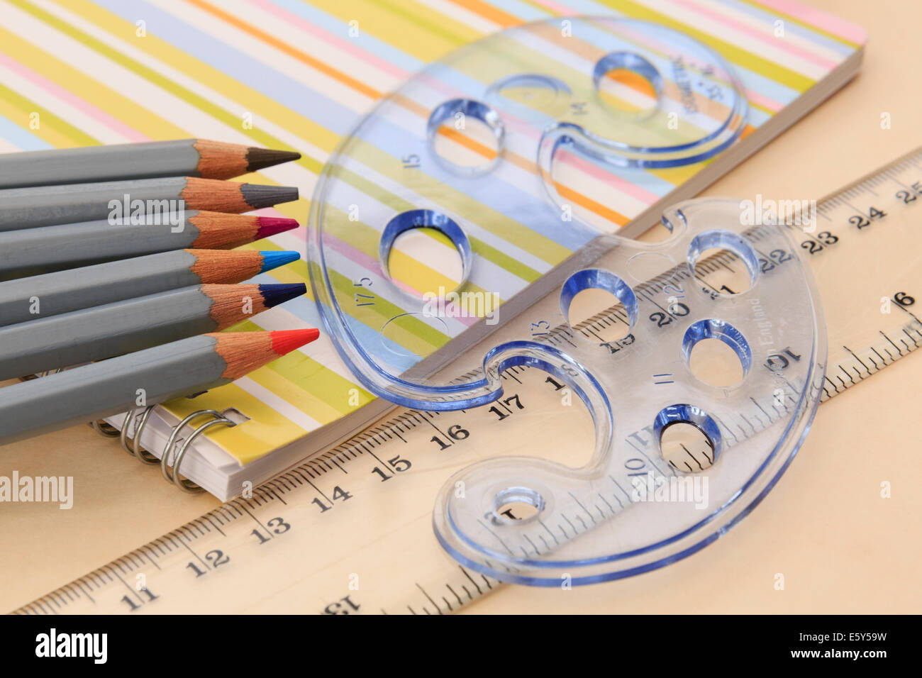 Educational equipment for drawing notebook, coloured pencils, ruler and geometric shapes stencil on a desktop. England - Stock Image
