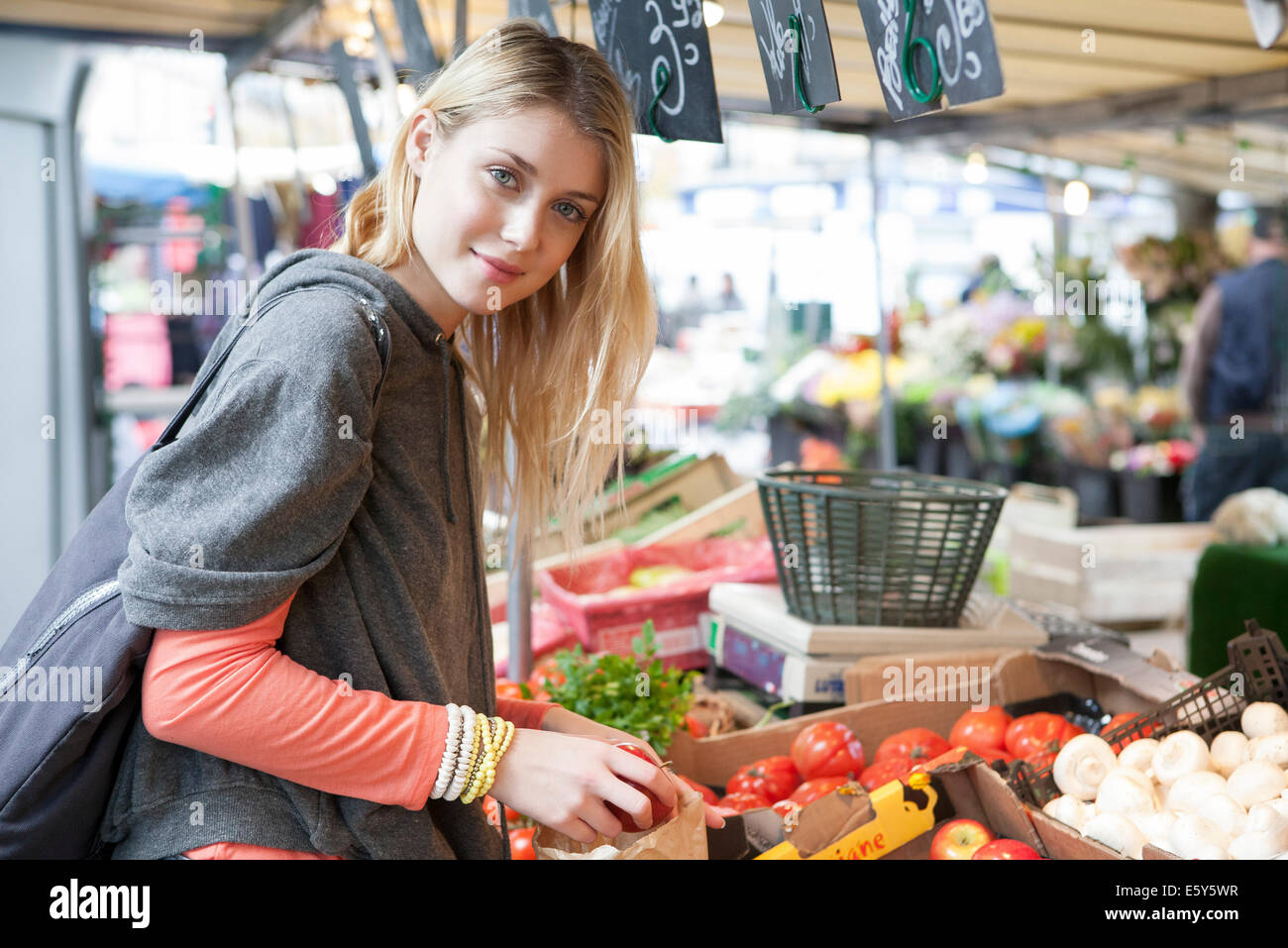 Young woman at greengrocer's shopping for fresh fruits and vegetables - Stock Image