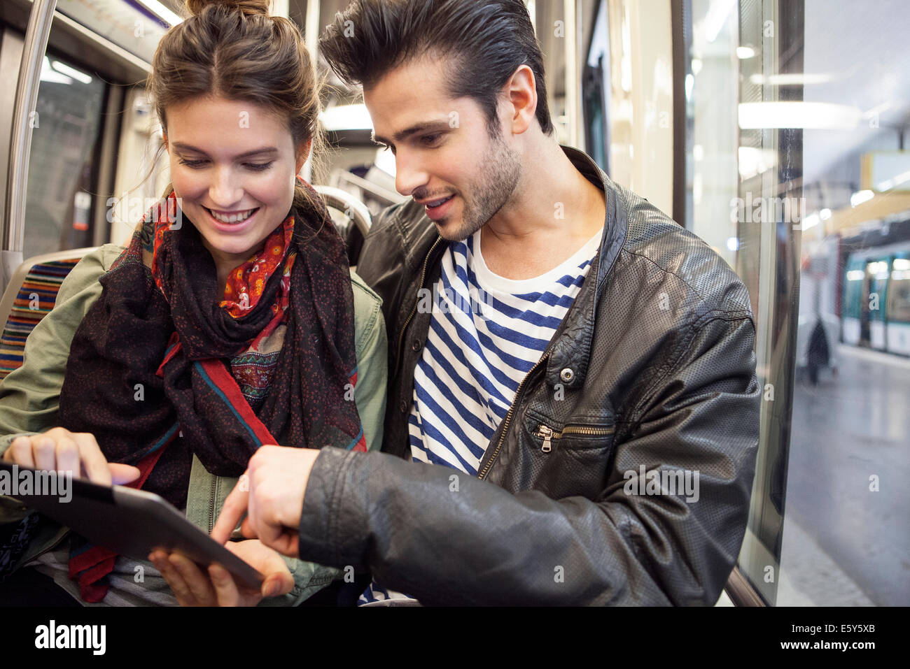 Young couple riding subway looking at digital tablet together - Stock Image