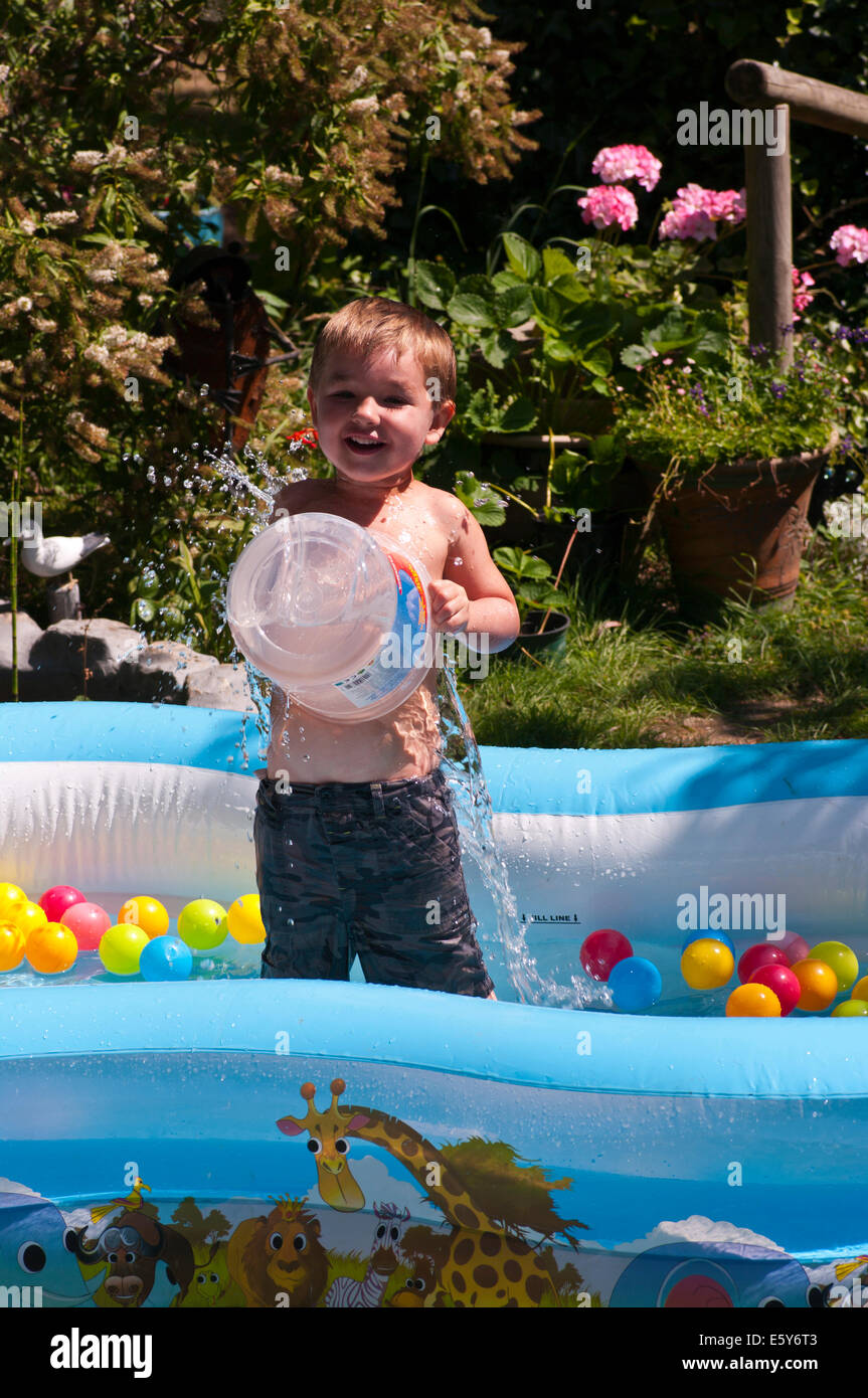 Little Boy Playing In A paddling Pool On a Hot Day Stock Photo