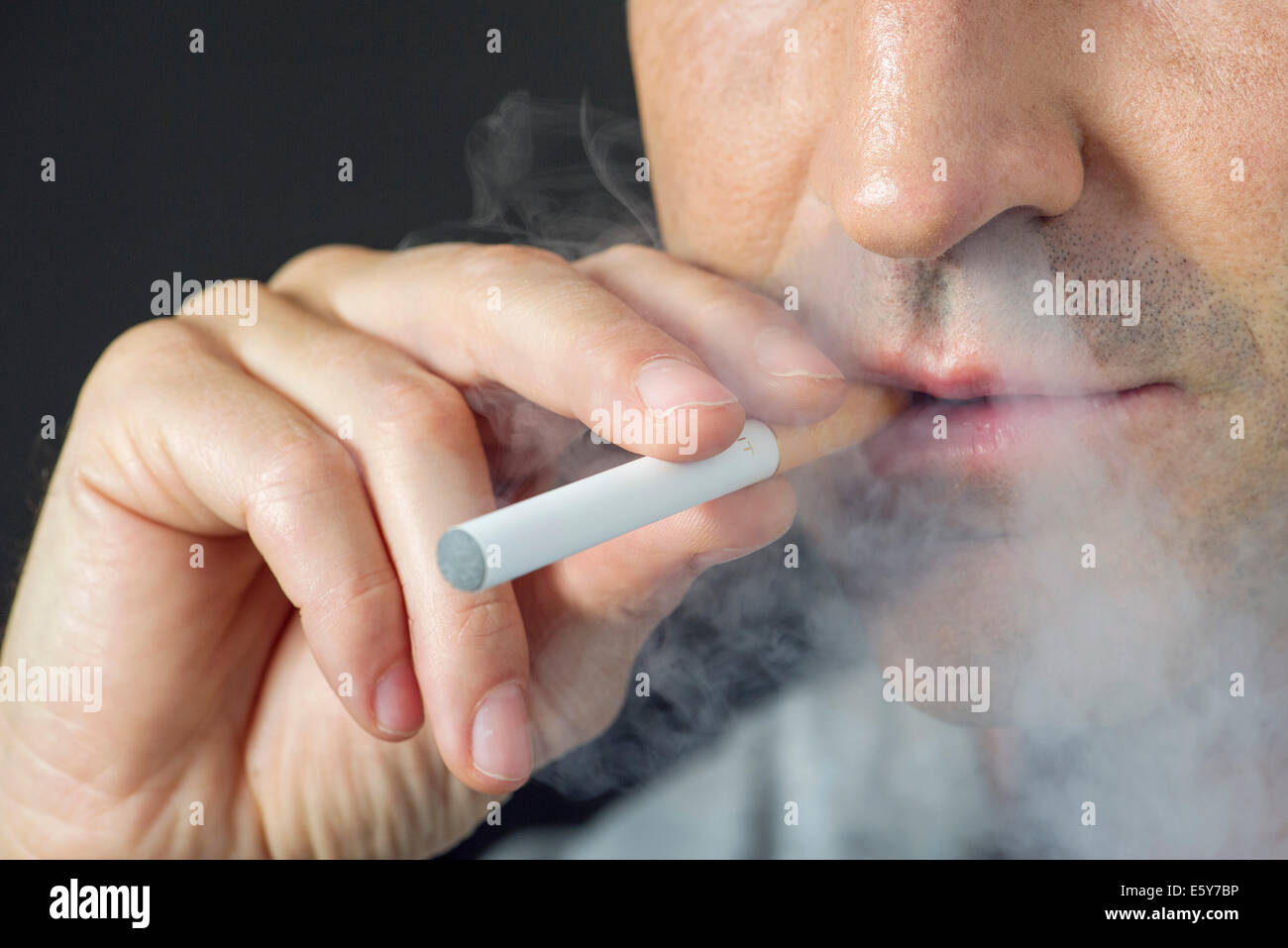 Man smoking electonic cigarette, cropped - Stock Image