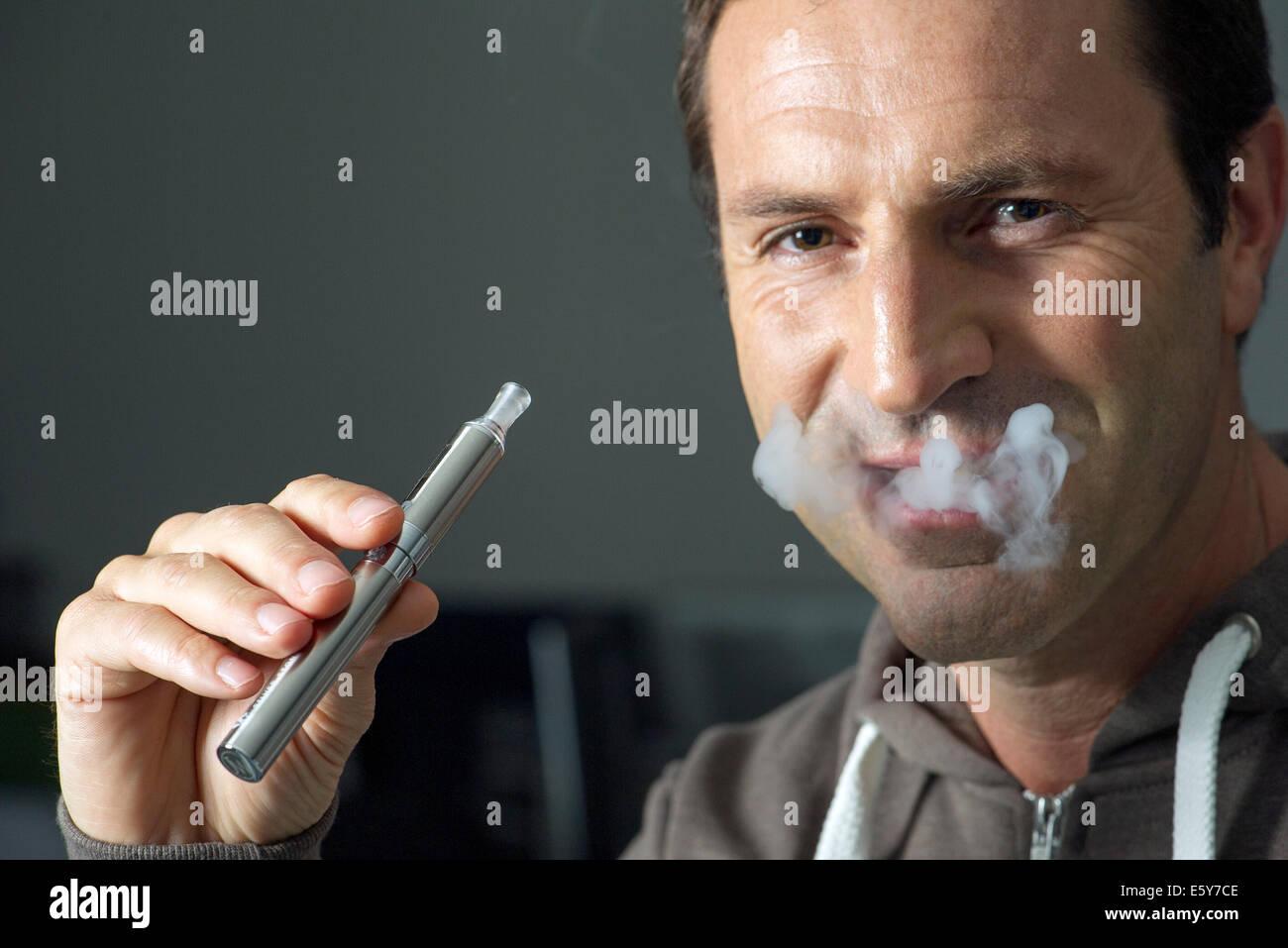 Man smoking electonic cigarette, exhaling smoke - Stock Image