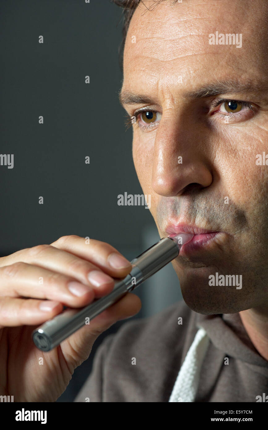 Man smoking electonic cigarette - Stock Image