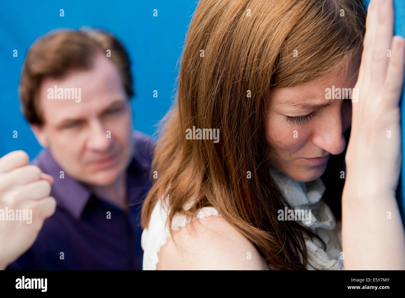 Tearful woman with her back to an aggressive man waving a clenched fist at her. Stock Photo