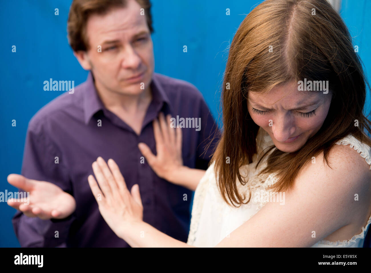 Tearful woman rejecting the advances of a man by keeping him at arms length. - Stock Image