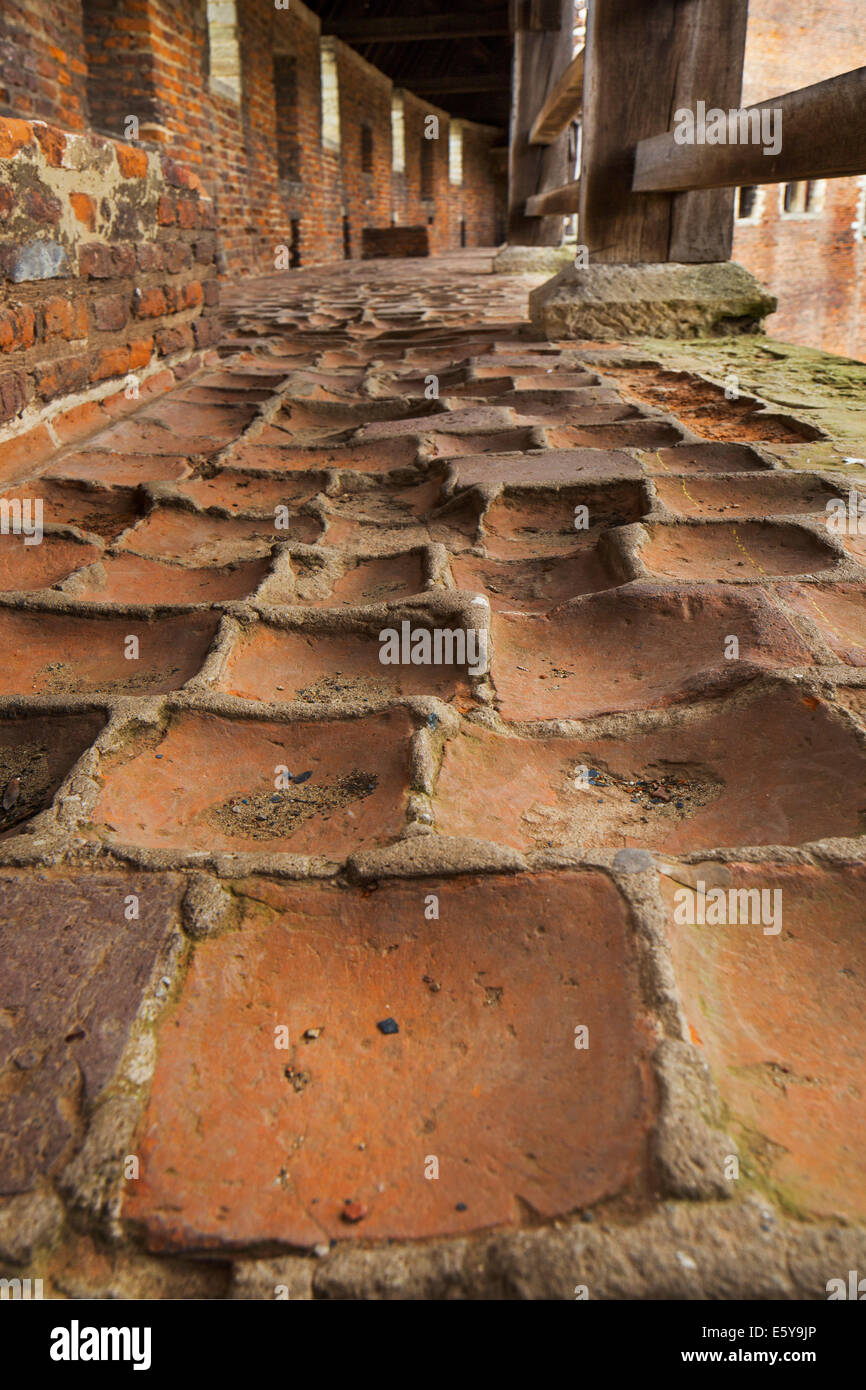 Worn-out red bricks in corridor and inner court of the medieval Beersel Castle, Belgium - Stock Image