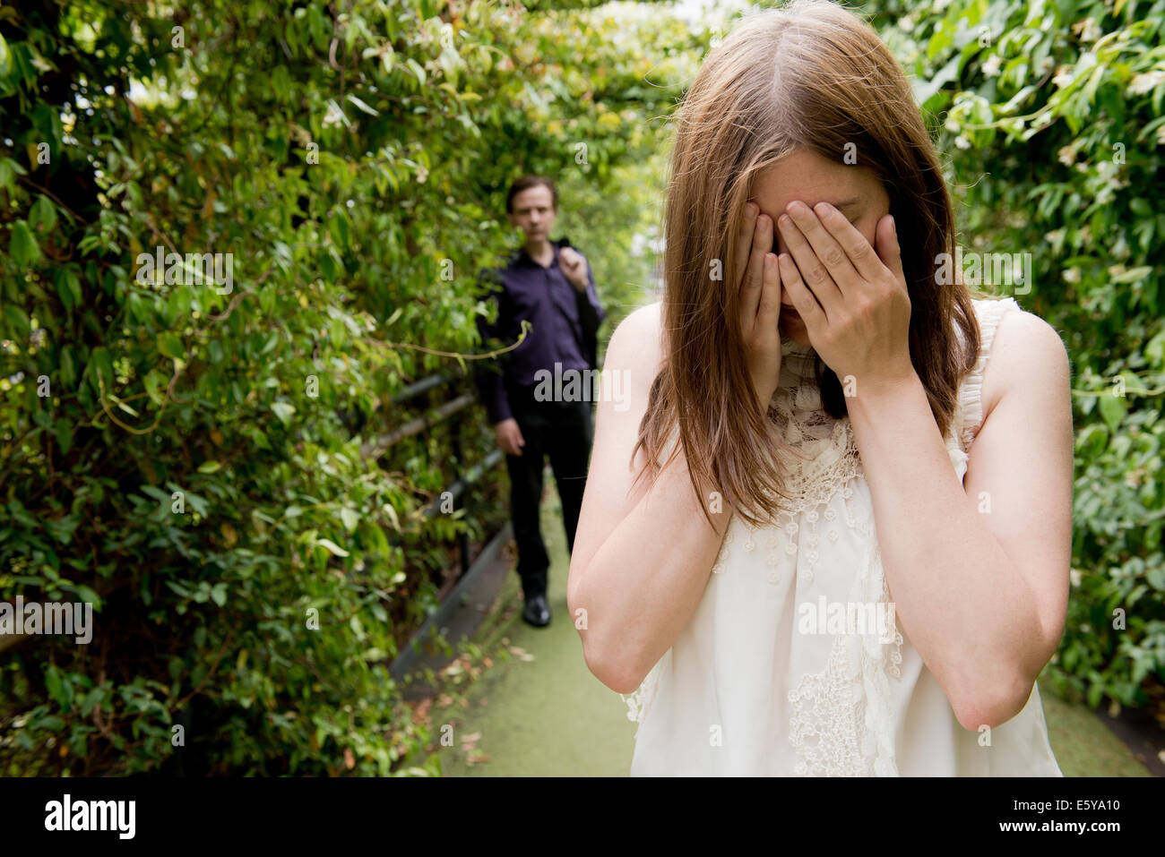 Tearful woman with hand on her face and man standing in the background. - Stock Image