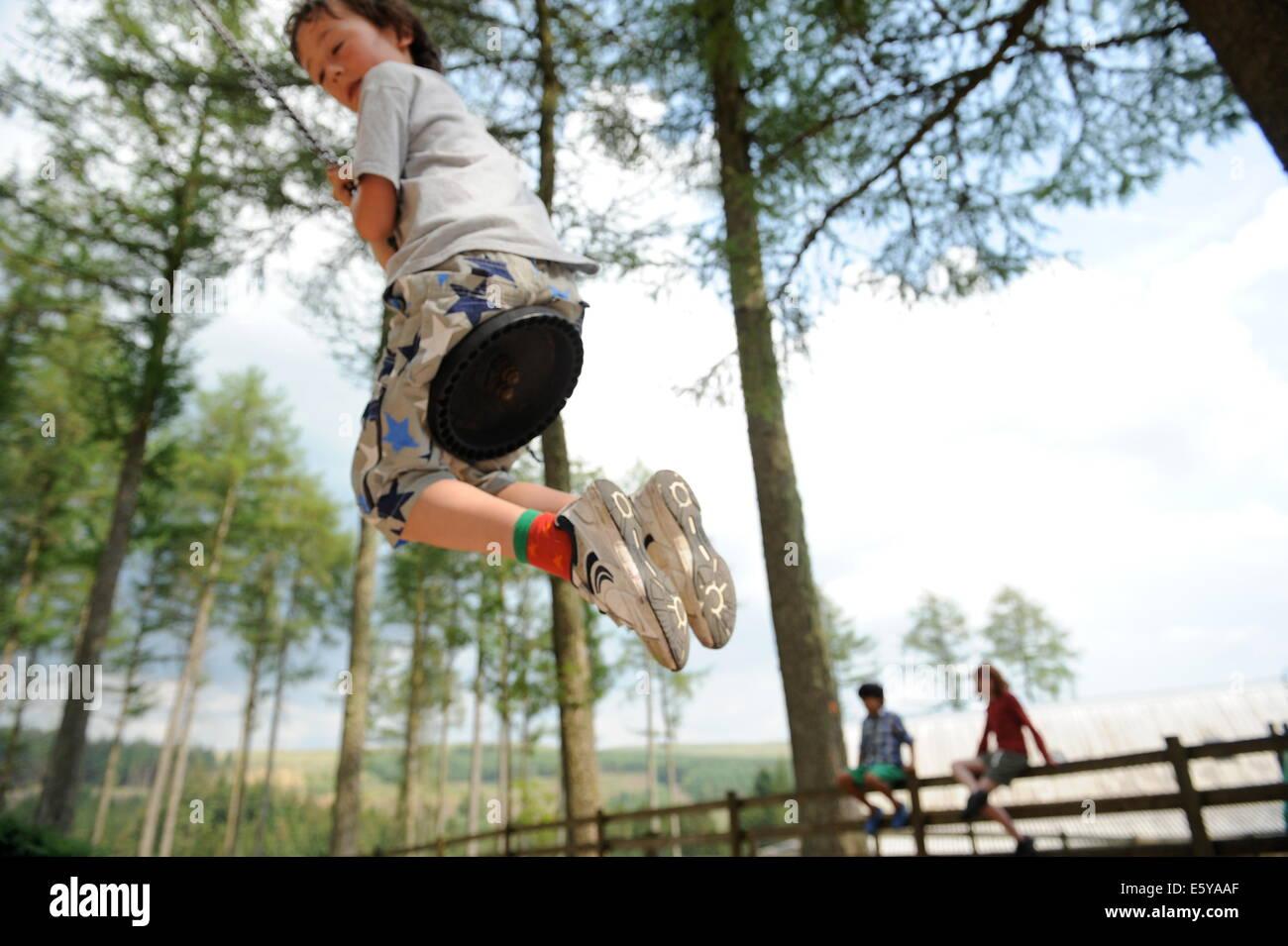School friends swinging in the adventure park at Garwnant Forest, Powys near Merthyr Tidfil, wales Stock Photo