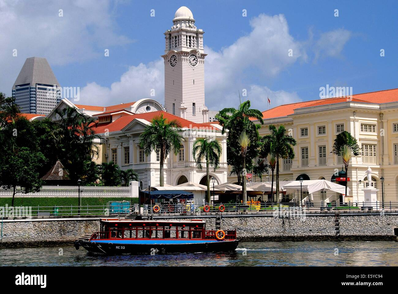 SINGAPORE:  A tour boat on the Singapore River passes the Asian Civilisations Museum and Victoria Theatre clock - Stock Image