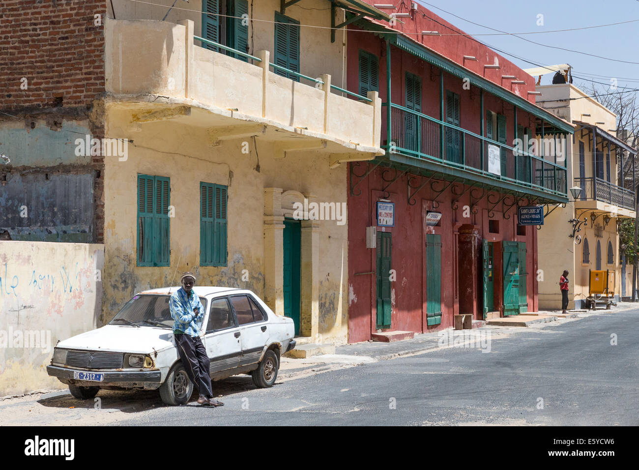 Man resting on car in historic, St. Louis, Senegal Stock Photo