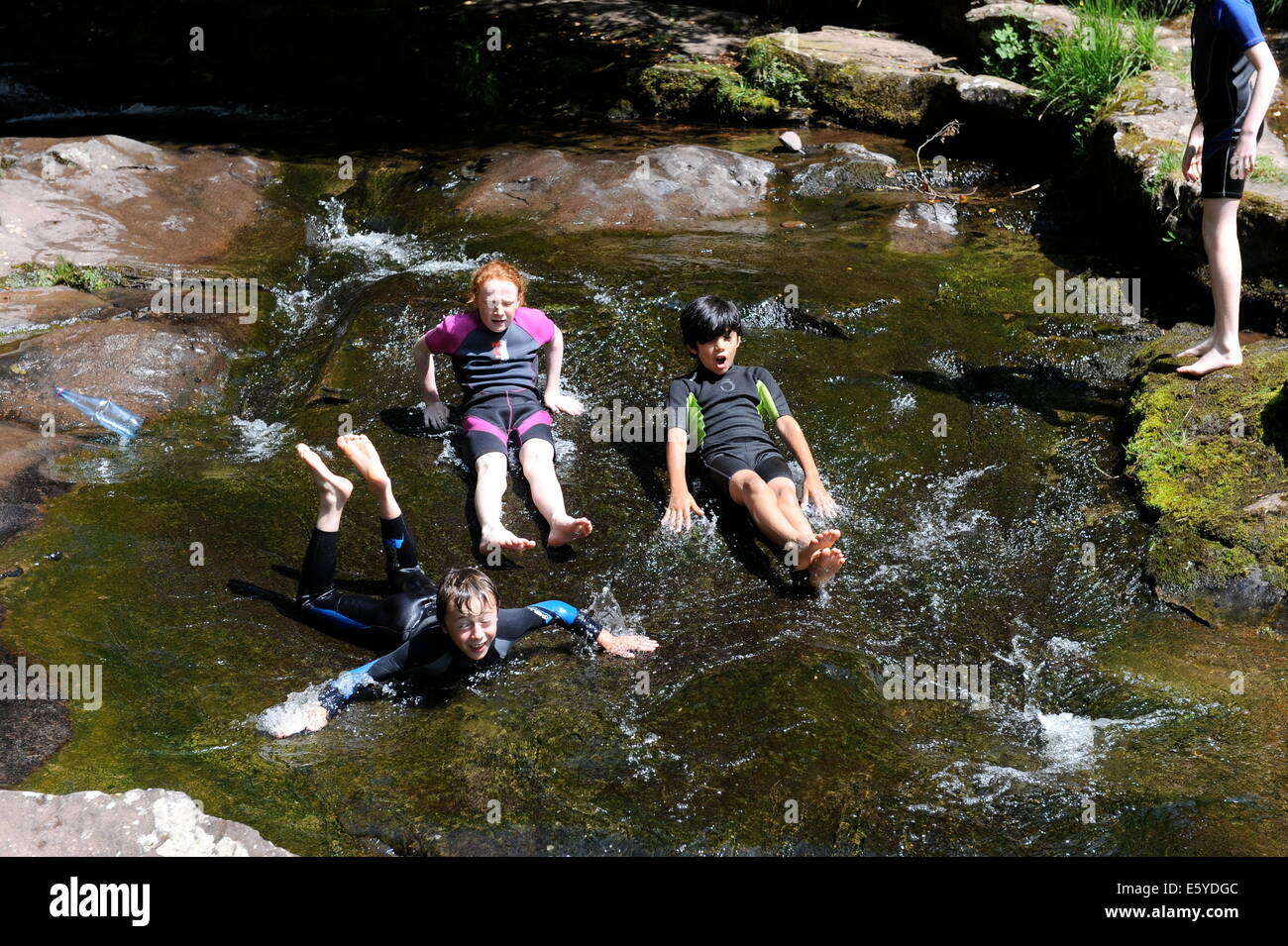 Young friends playing together at Caerfanell near Talybont reservoir, Powys, Wales - Stock Image