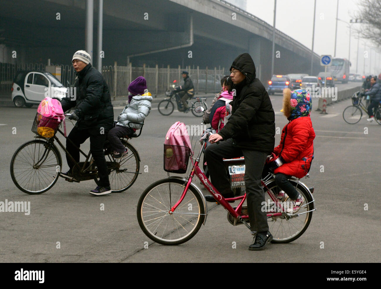 Two men riding bicycles to send their children to school in the morning in Beijing enveloped with smog. - Stock Image
