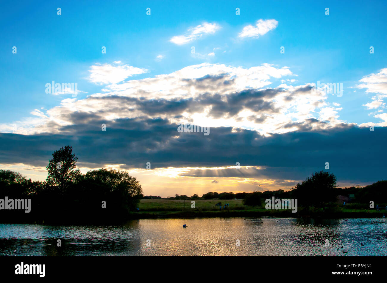 Nantwich lake just before sunset with the sun shining through some dark clouds - Stock Image