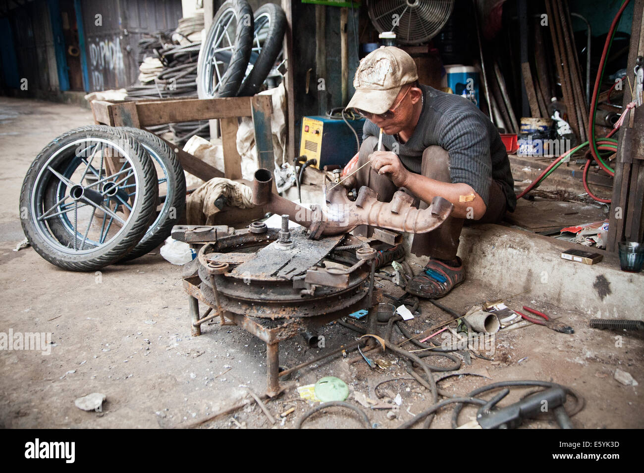 Welder of Indonesian ethnicity working in gritty backstreets of Pontianak in Indonesian Borneo. Undeveloped countries - Stock Image