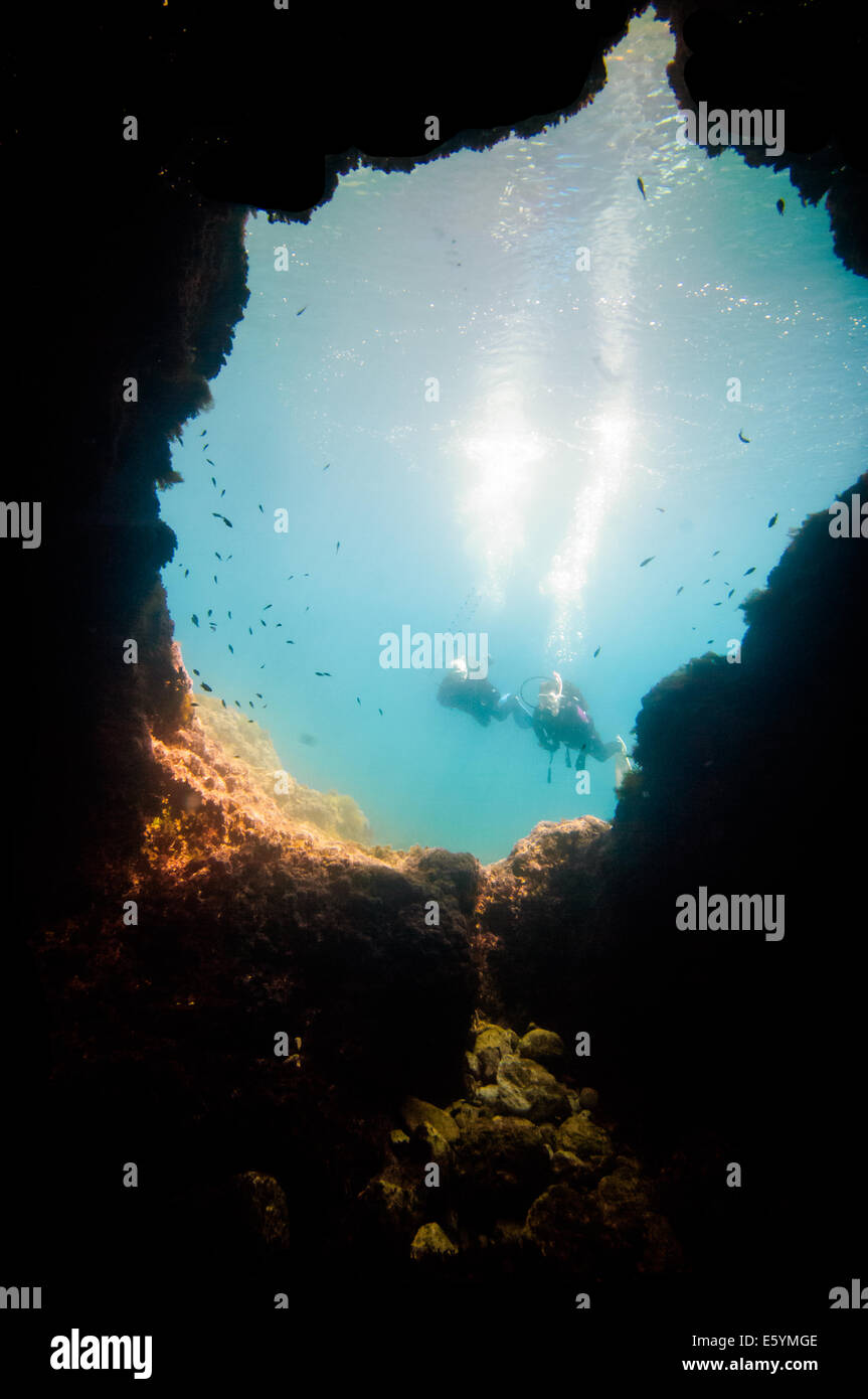 Scuba divers swimming underwater in bright blue Mediterranean Sea - Stock Image