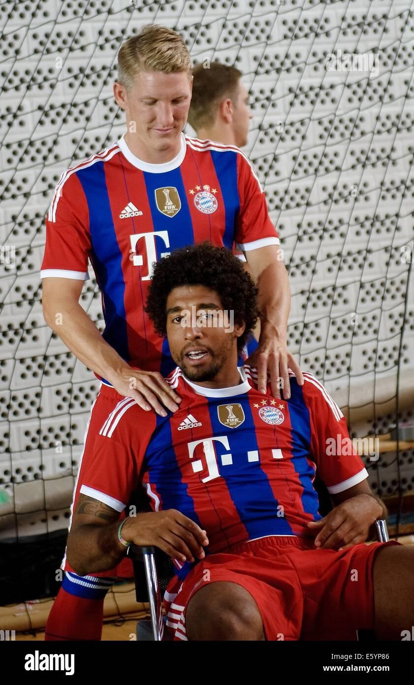 Bastian Schweinsteiger (L) massages Dante of Bundesliga soccer club Bayern Munich during the official photo opportunity - Stock Image