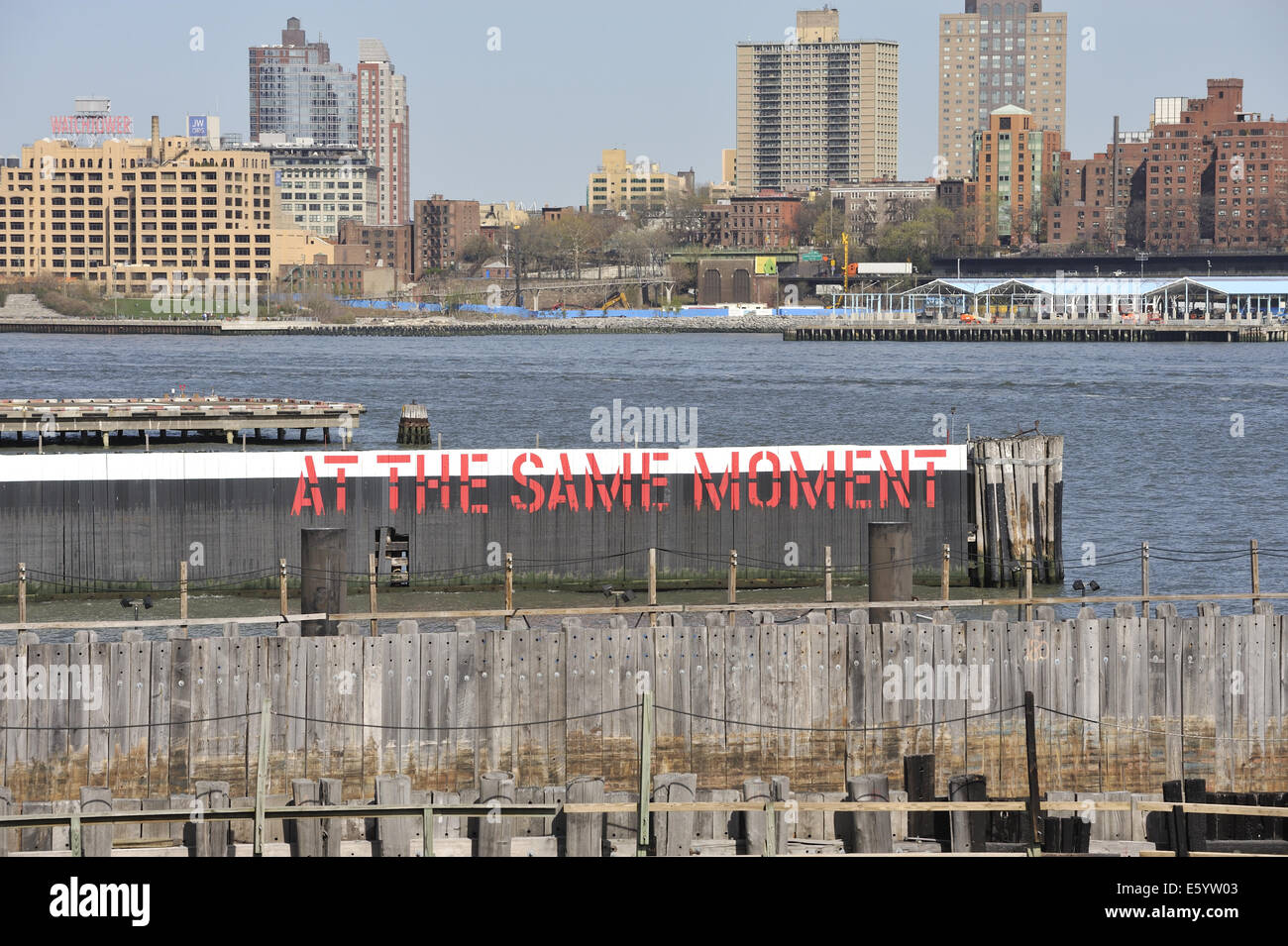 Lawrence Weiner's conceptual artwork 'At The Same Moment', painted on pilings on the East River, New - Stock Image