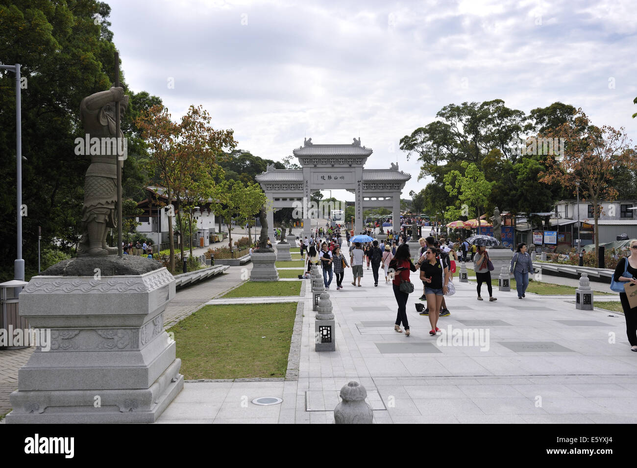 The Bodhi Path, with statues of the 12 Divine Generals, and pai lau in the distance. Tian Tan Buddha, Ngong Ping, Stock Photo