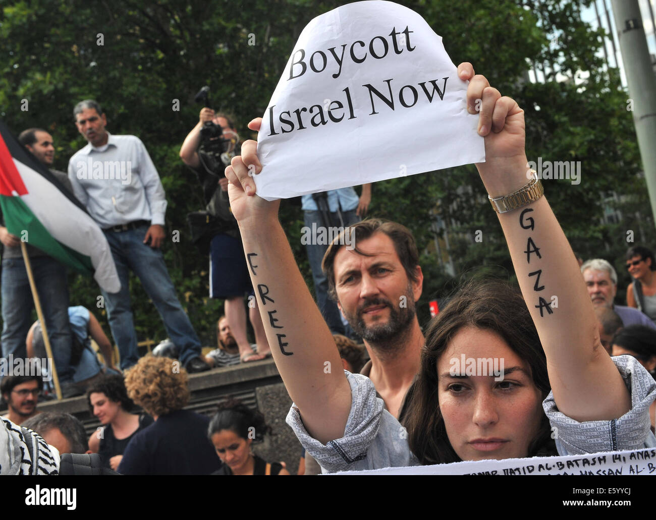 Berlin, Germany. 09th Aug, 2014. A woman holds up a sign reading 'Boycott Israel Now' outside of the Axel - Stock Image