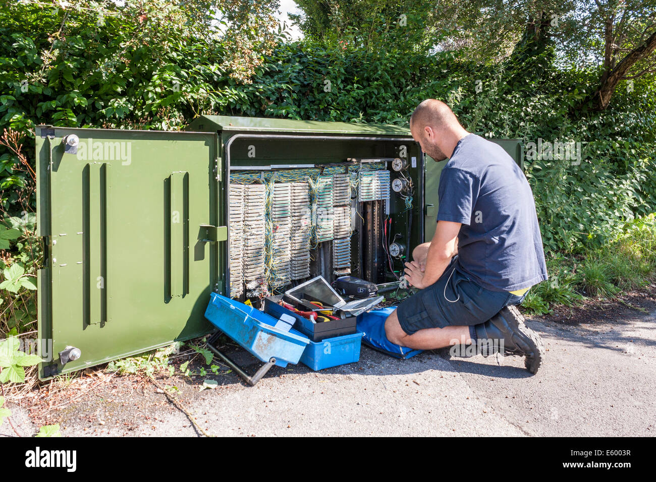 Engineer working for BT Openreach corrects broadband faults at a roadside terminal. - Stock Image