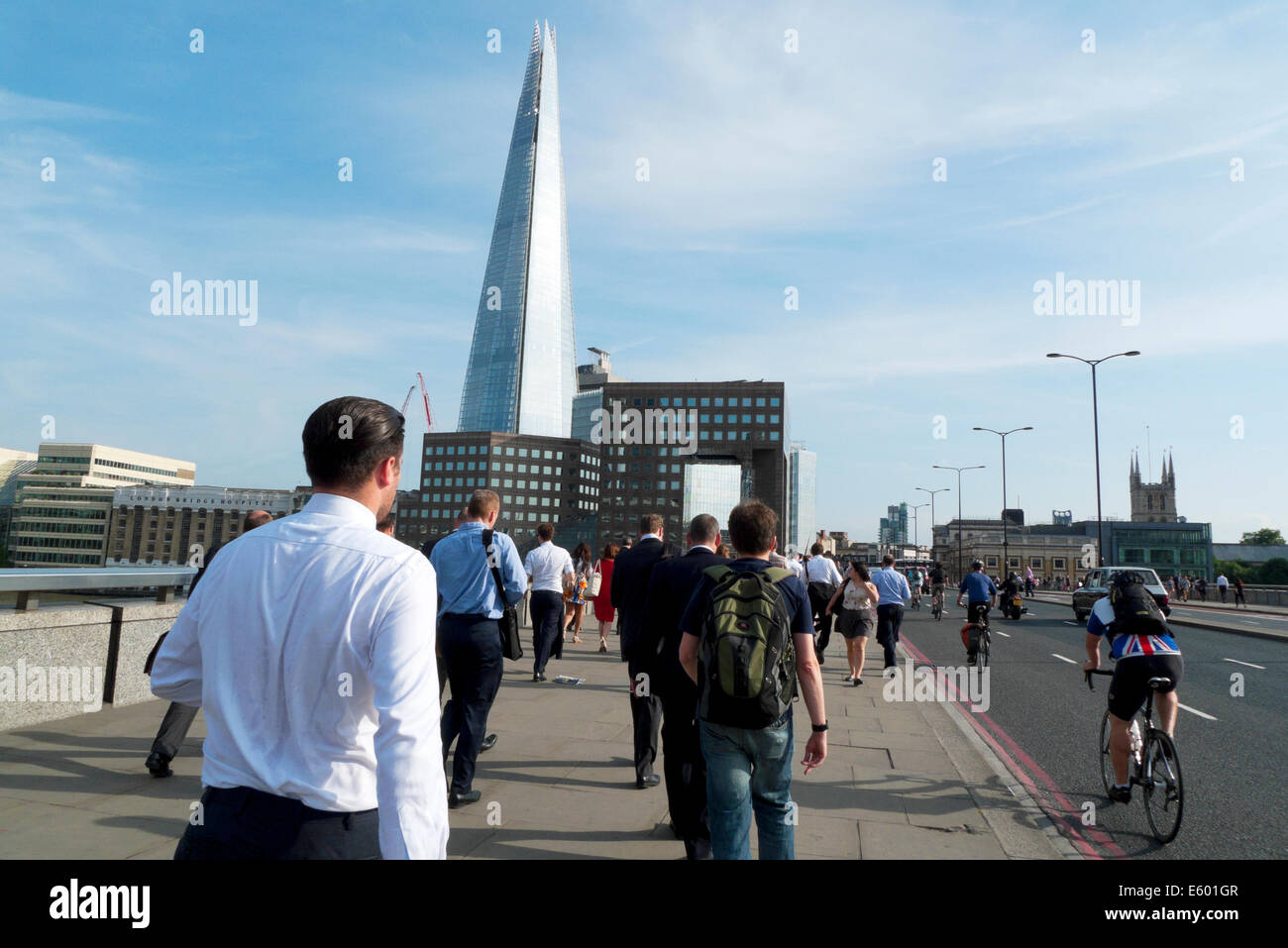 City of London businessman in crowd of office workers walking home over  London Bridge after work with view of Shard - Stock Image