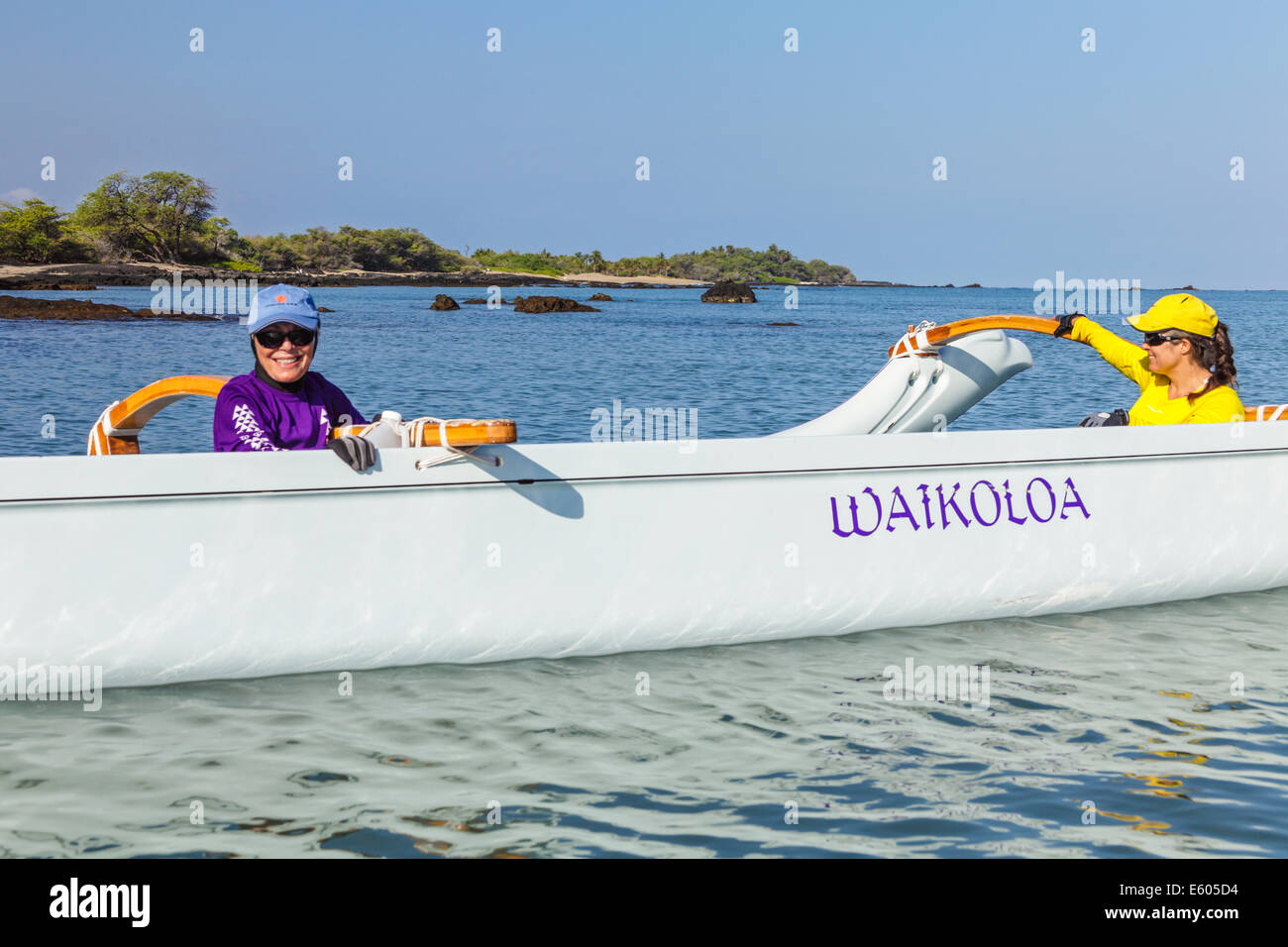 Women by outrigger canoe at Anaehoomalu Bay in Waikoloa on the Big Island of Hawaii before practice - Stock Image