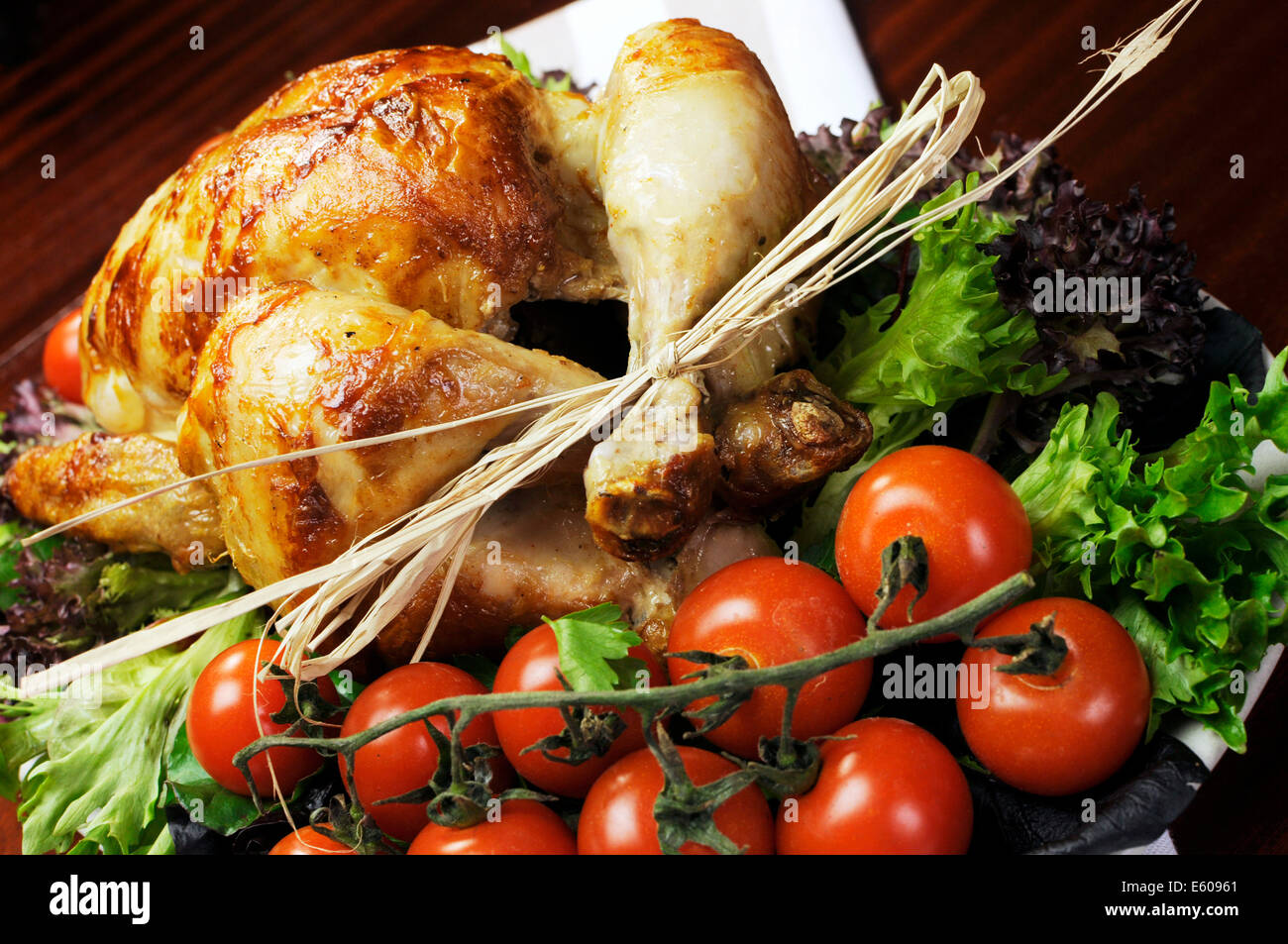 Platter of delicious roast chicken turkey with salad greens and red tomatoes on the vine. - Stock Image