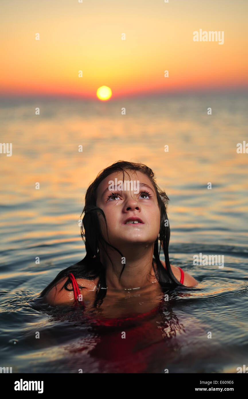 Young girl in red dress standing in sea at sunset Stock Photo