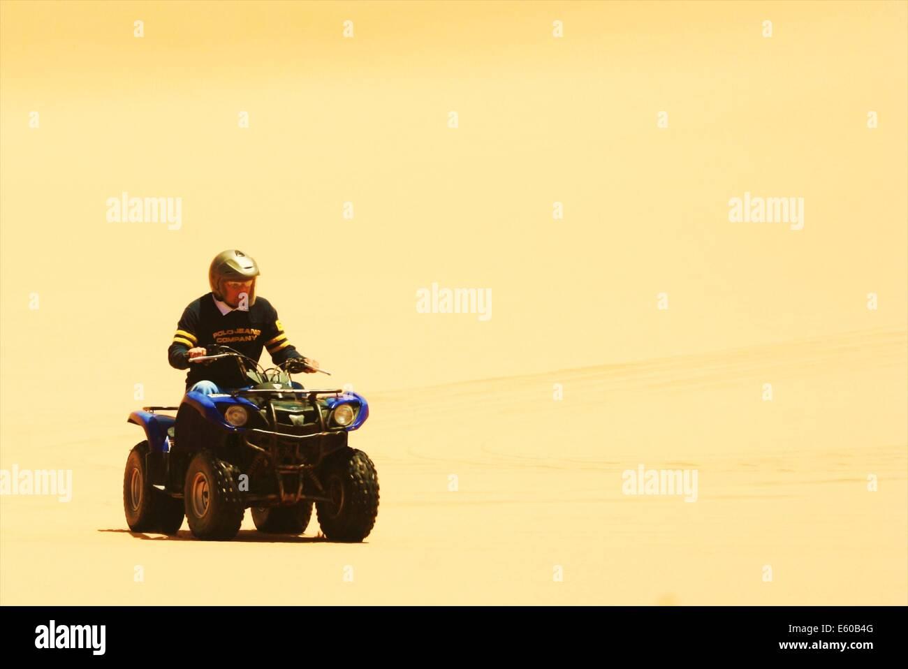 ATV Quad biking through the sand dunes of the Namib desert, near Swakopmund, Namibia - Stock Image