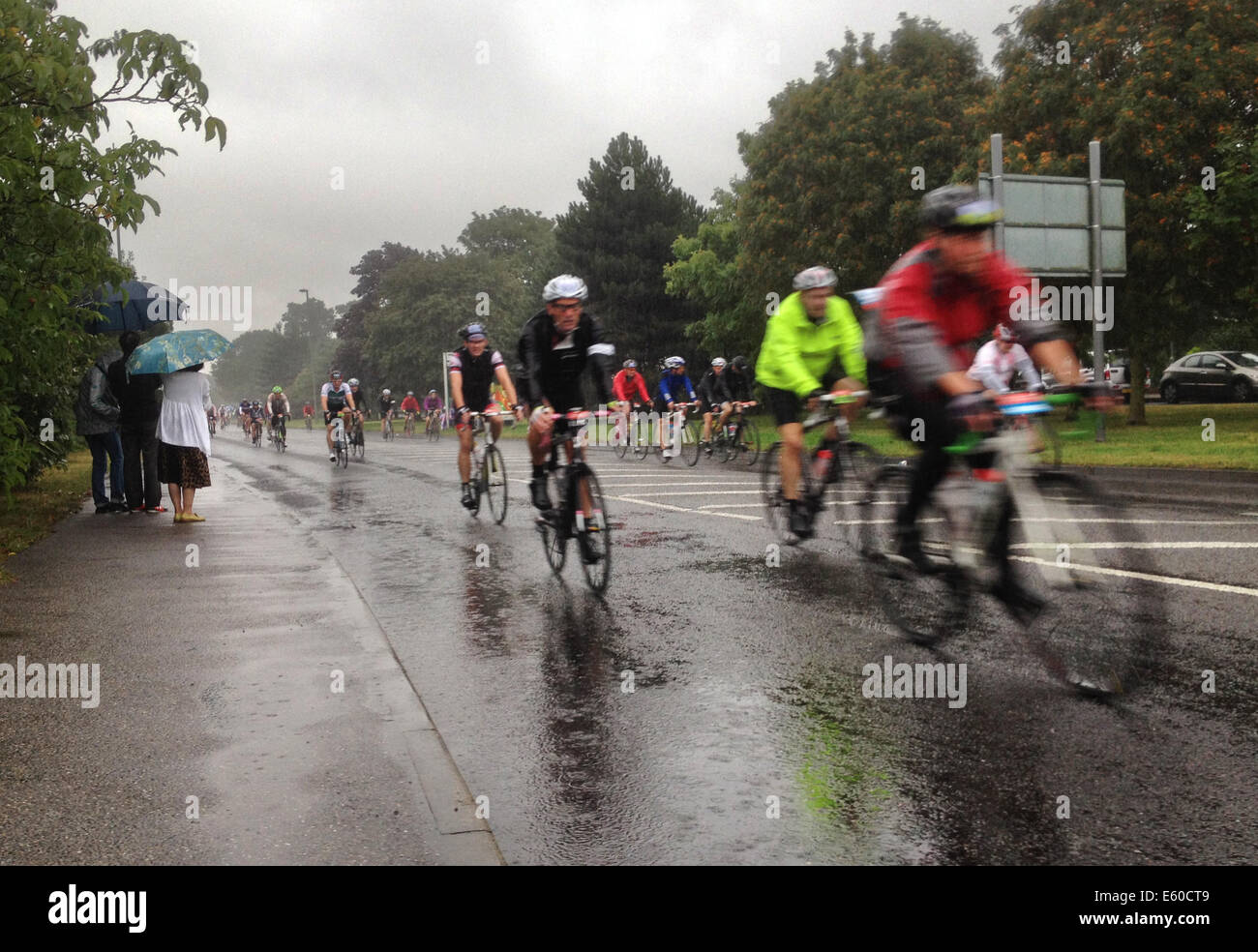 West Molesey, Surrey, UK. 10th Aug, 2014. Cyclists in the Prudential Ride London face torrential rain as they pass - Stock Image