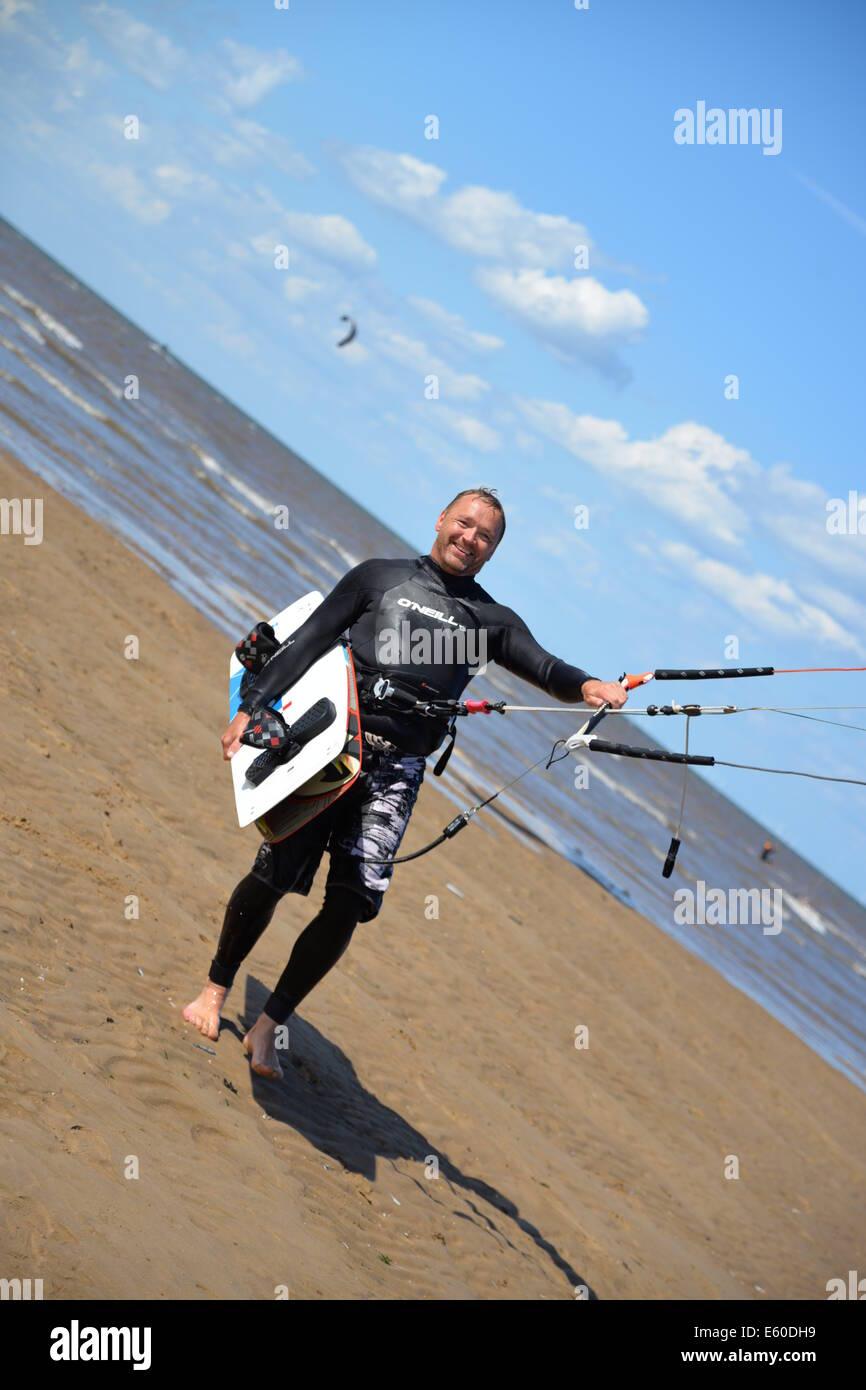 Smiling kite boarder walking from sea Hunstanton , Norfolk, UK, England - Stock Image