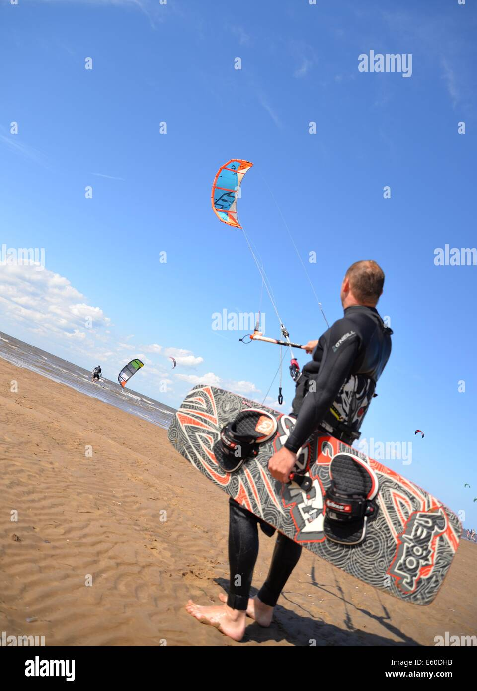 Man looking up towards his kite before he gets into the sea Hunstanton , Norfolk, UK, England - Stock Image