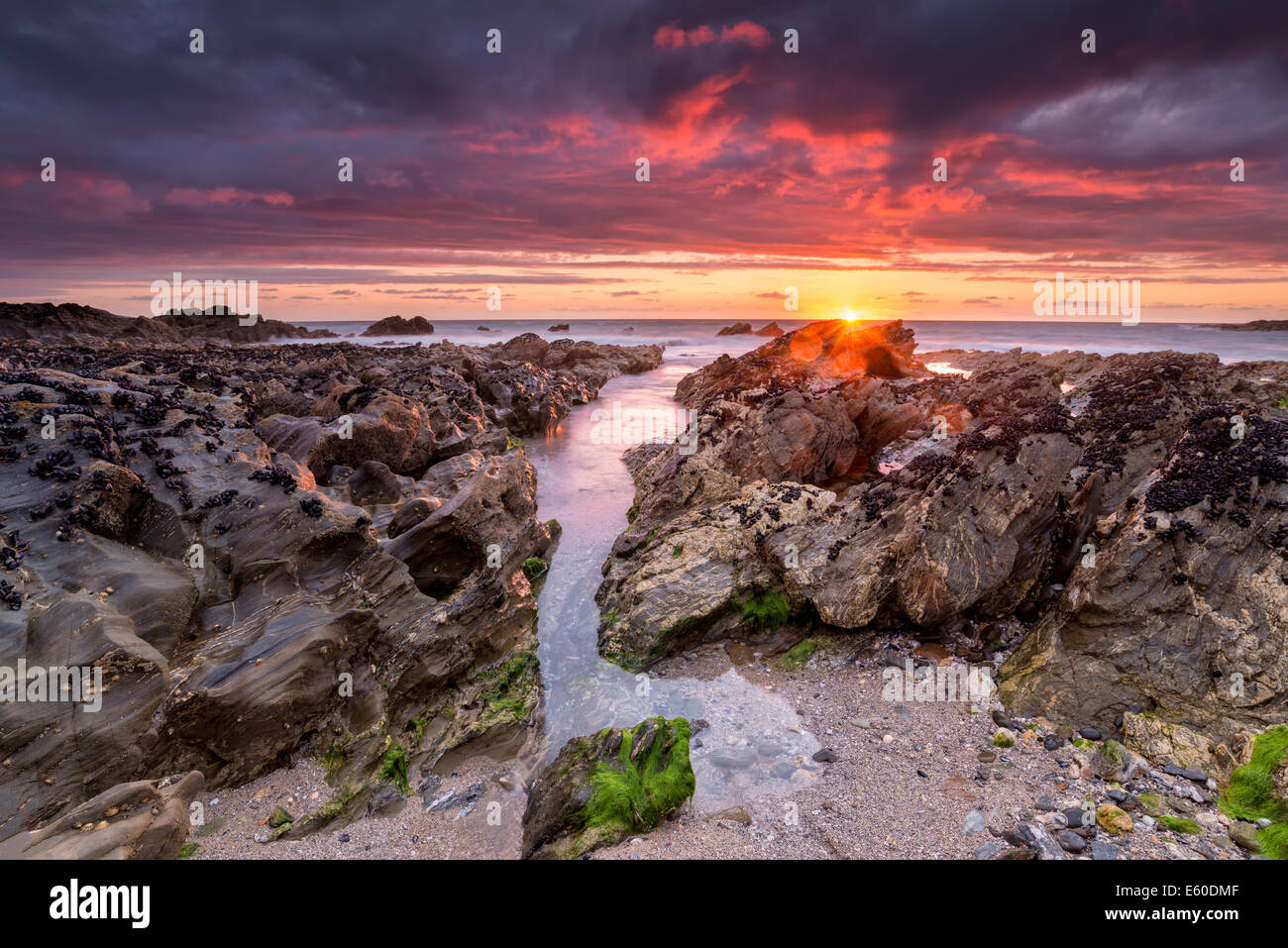 Dramatic fiery sunset on Little Fistral beach at Newquay in Cornwall - Stock Image